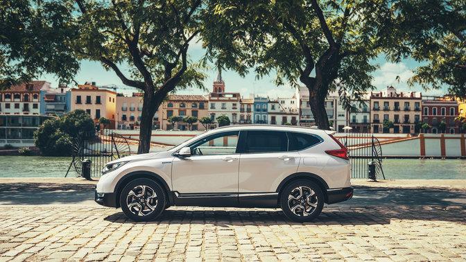Vista laterale di un'auto Honda CR-V Hybrid ambientata in una strada.