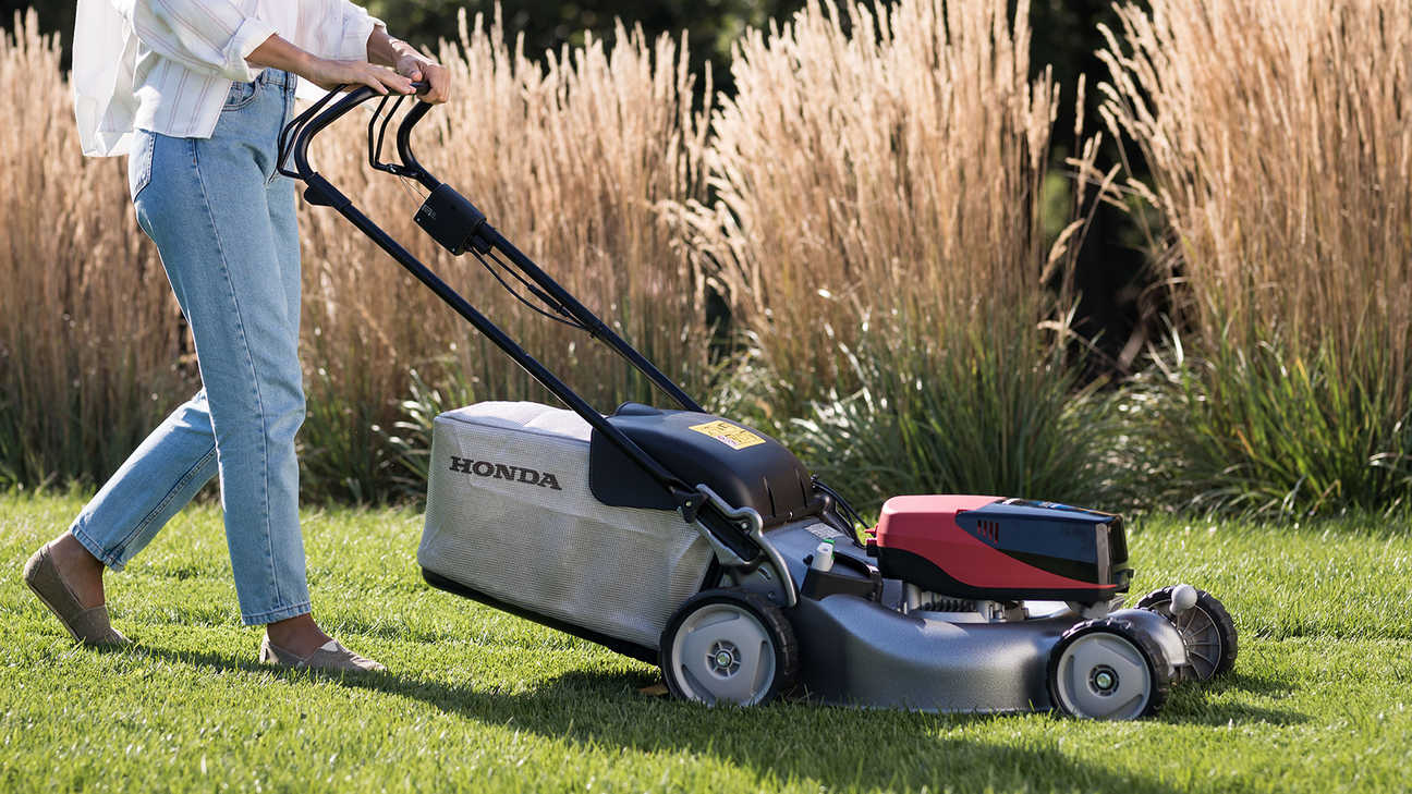 Model demonstrating Honda izy-On lawnmower in garden location.