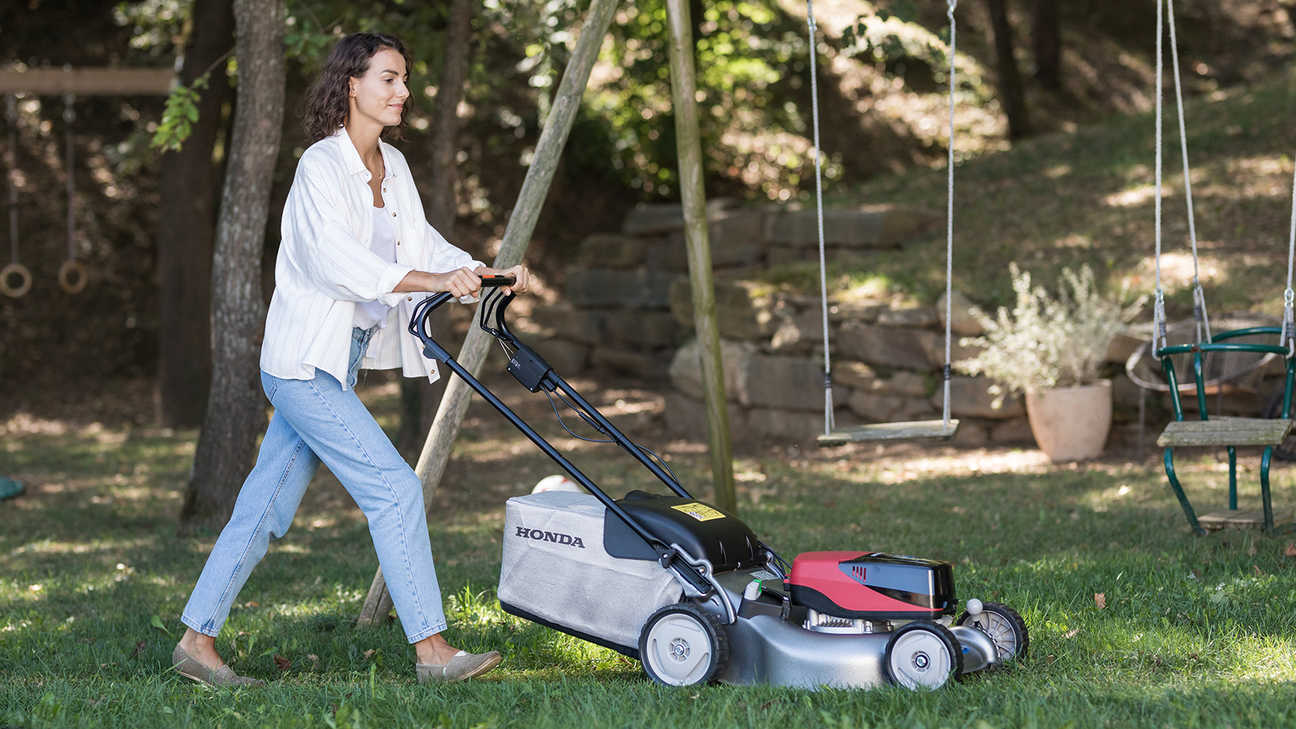 Model using Honda's cordless lawn mower in garden location.