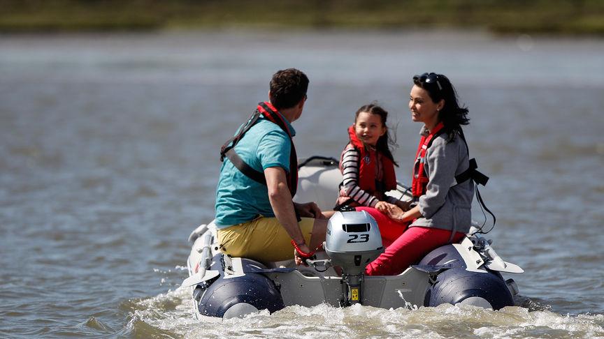 Famiglia sul lago su una barca con Honda BF2.3.