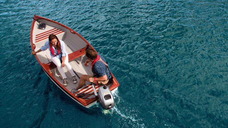 Un uomo e una donna in barca e utilizzano il motore BF2.3 per navigare