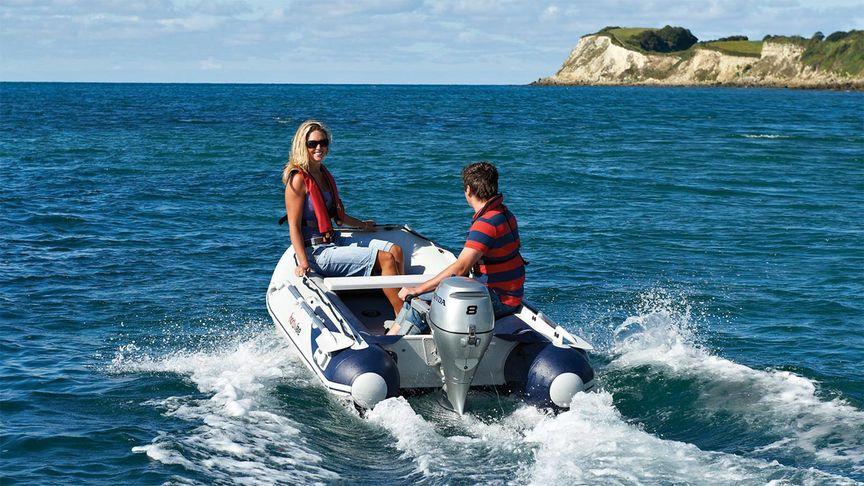 Madre e figlio a bordo di una barca Highfield spinta da un motore fuoribordo Honda BF8