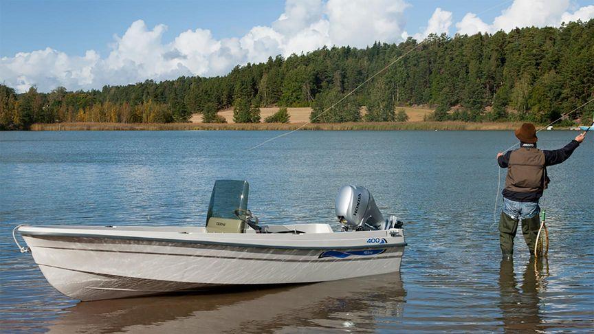 Uomo che pesca accanto a una piccola barca con un motore fuoribordo Honda