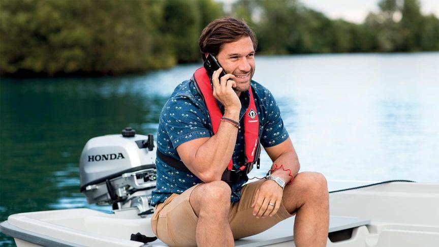 Uomo su una piccola barca che ricarica il telefono dal suo motore fuoribordo Honda mentre sta parlando