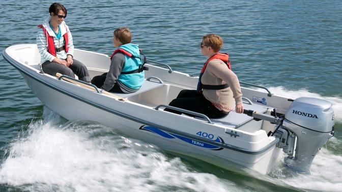 Barca con motore Honda, utilizzata da modelli, località costiera.