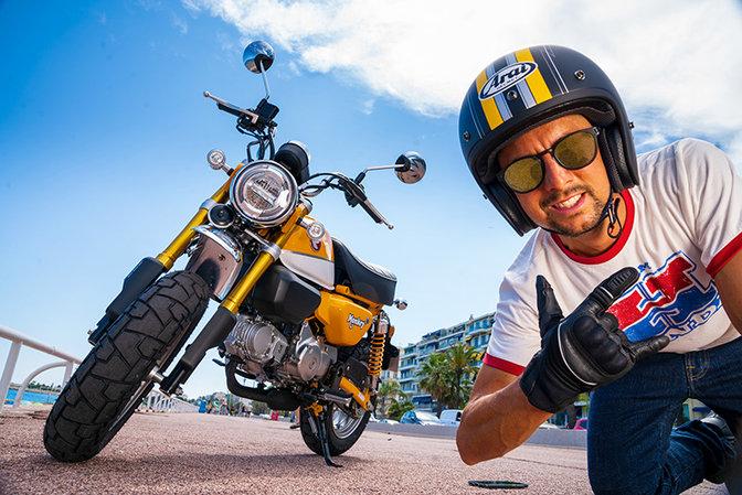 Monkey 125cc, inquadratura anteriore destra di tre quarti, uomo con casco sullo sfondo