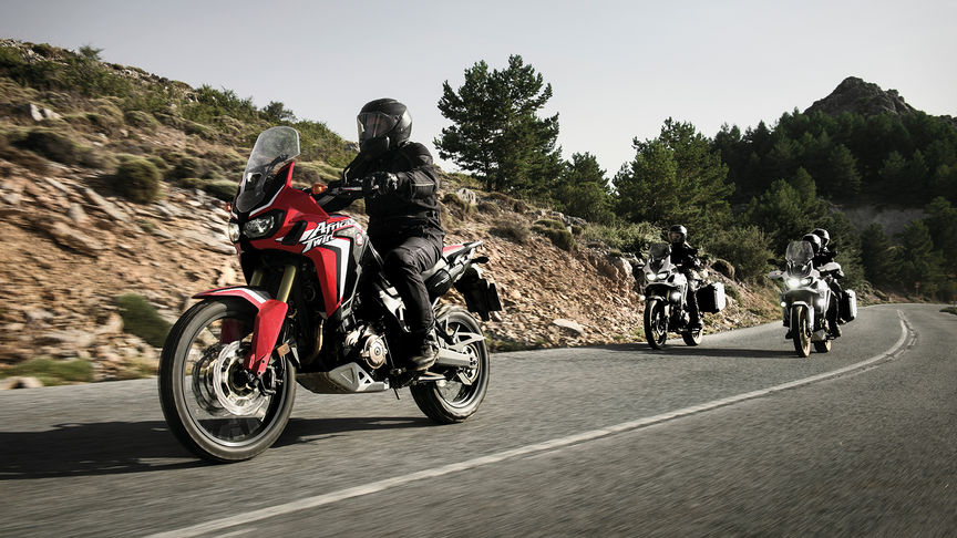 Tre moto Africa Twin in curva