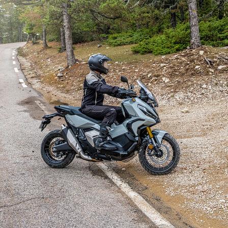 Honda X-ADV, lato destro, con guidatore, moto grigia, sentiero nella foresta