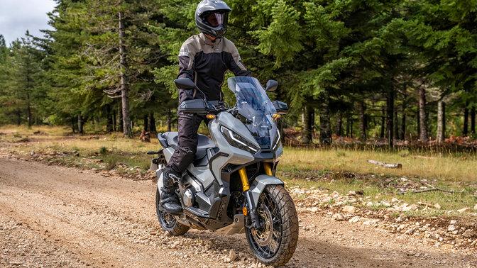 Honda X-ADV, vista di tre quarti anteriore destra, con guidatore, su strada nella foresta