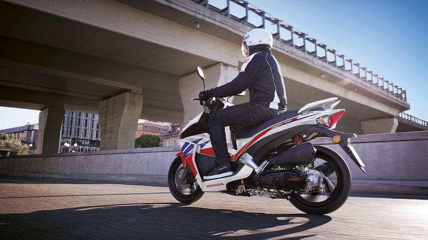 Inquadratura posteriore di tre quarti dello scooter Honda Vision Repsol con pilota. Lato sinistro (su strada).
