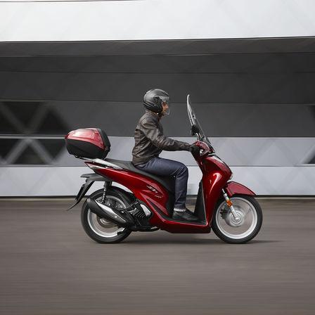 Honda SH150i, lato destro, con pilota, in movimento in città