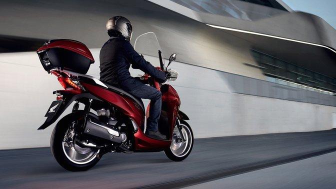 Vista posteriore di tre quarti di uno scooter Honda SH300i con portaoggetti superiore, in città.