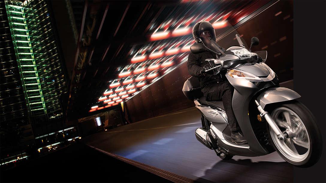 SH300i in corsa durante la notte in una strada tranquilla e illuminata
