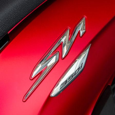 Honda SH350i, primo piano sul logo SH, moto rossa