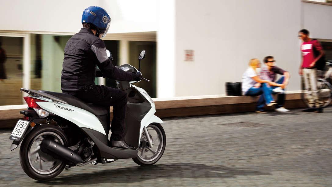 Inquadratura posteriore di tre quarti dello scooter Honda Vision 50 bianco con pilota. Lato destro (su strada).