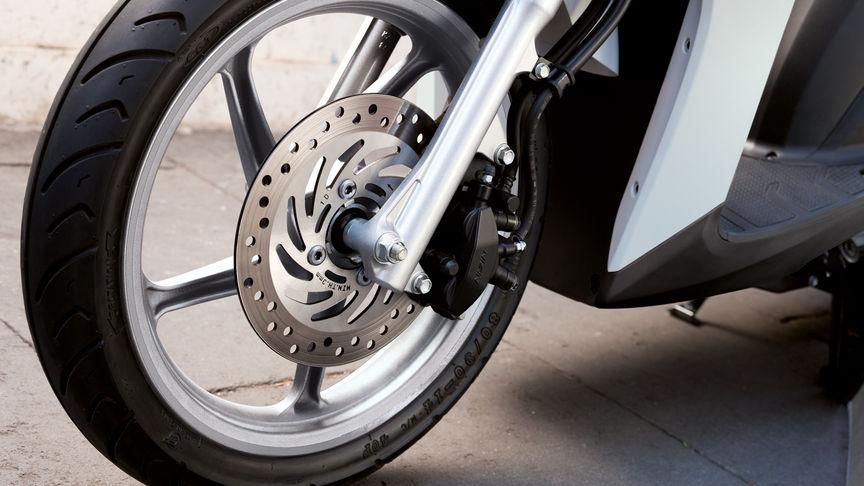Ruota anteriore dello scooter Honda Vision con freni CBS in evidenza. Lato sinistro.