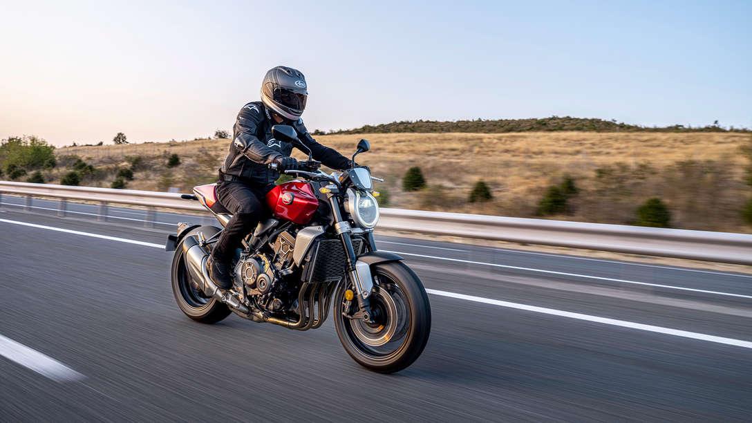 Honda CB1000R, vista di tre quarti posteriore destra, con un guidatore, moto rossa, su strada