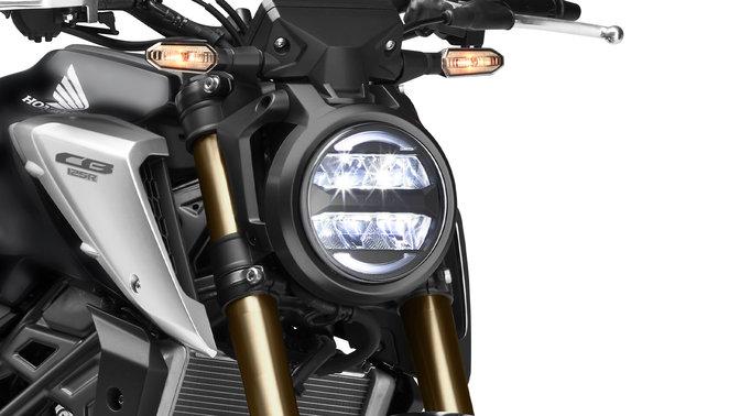 Honda CB125R, vista anteriore di tre quarti destra, primo piano sulle luci, scatto in studio, moto nera